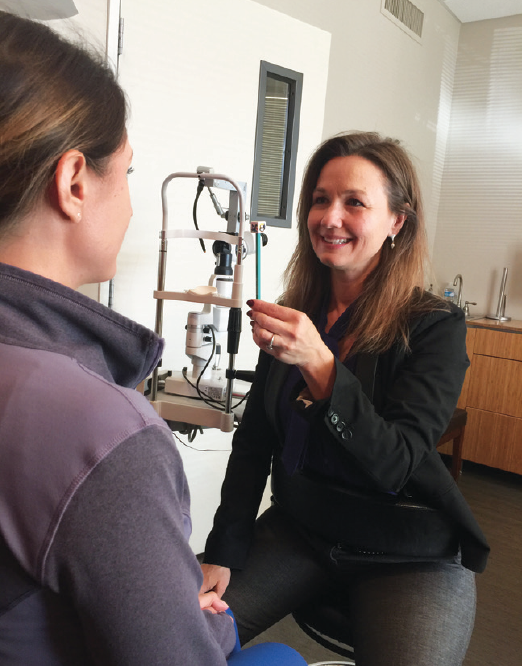 Figure 1. Dr. Polec (right) performs the near point convergence test, wherein the clinician slowly moves a pencil or finger toward a patient between the eyes. The test is one of three tests that provide crucial information about visual function and how well the eyes work together.